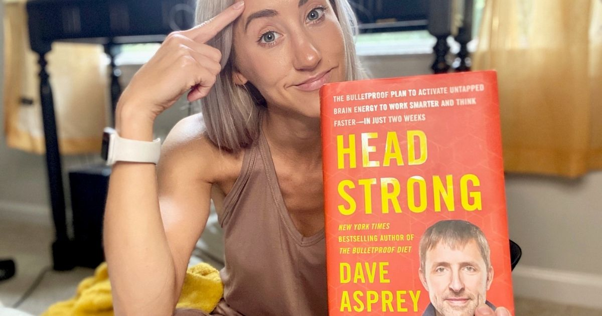 Woman holding a hard copy of Head Strong and pointing to her head