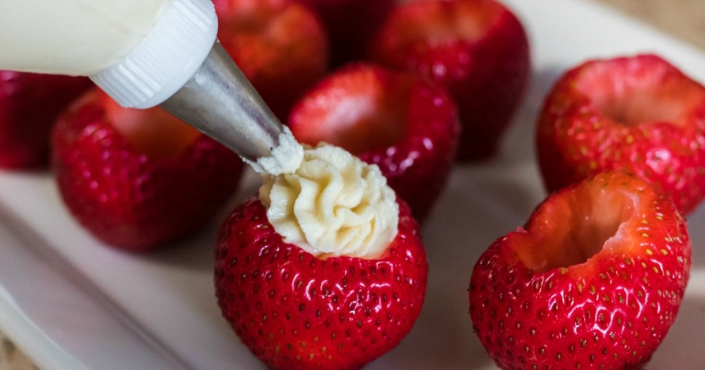 filling fresh strawberries with keto frosting