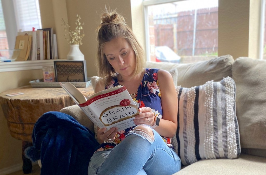 woman sitting on couch with legs crossed reading Grain Brain