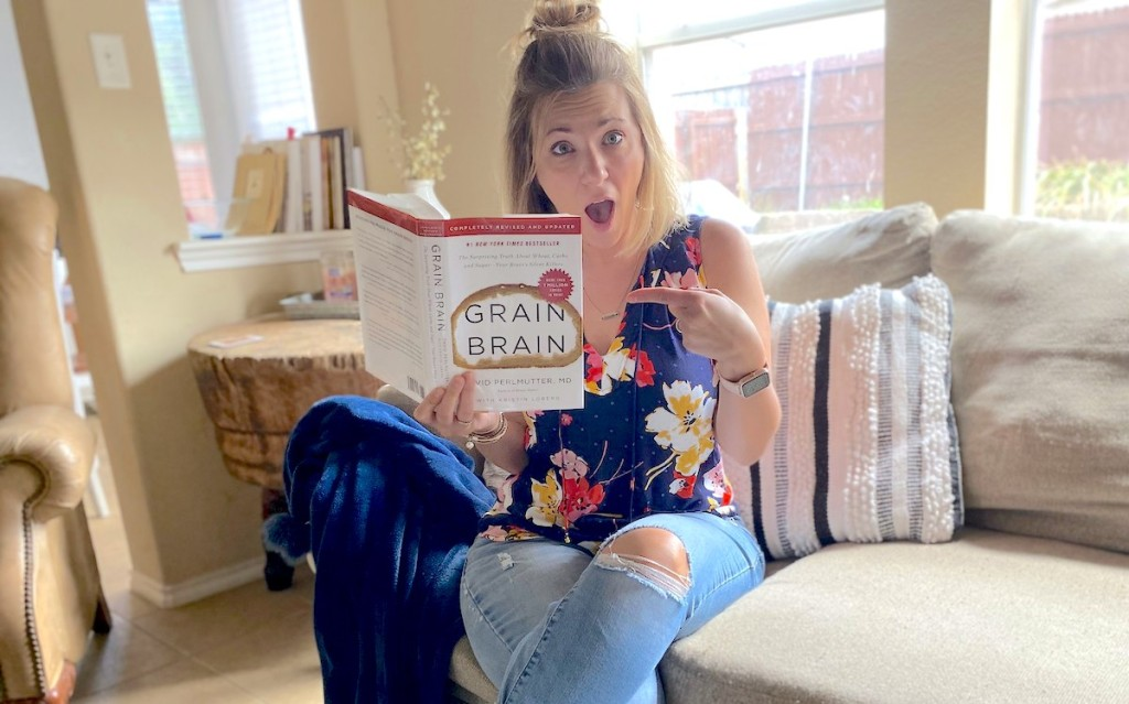 Woman sitting on couch pointing to grain brain book