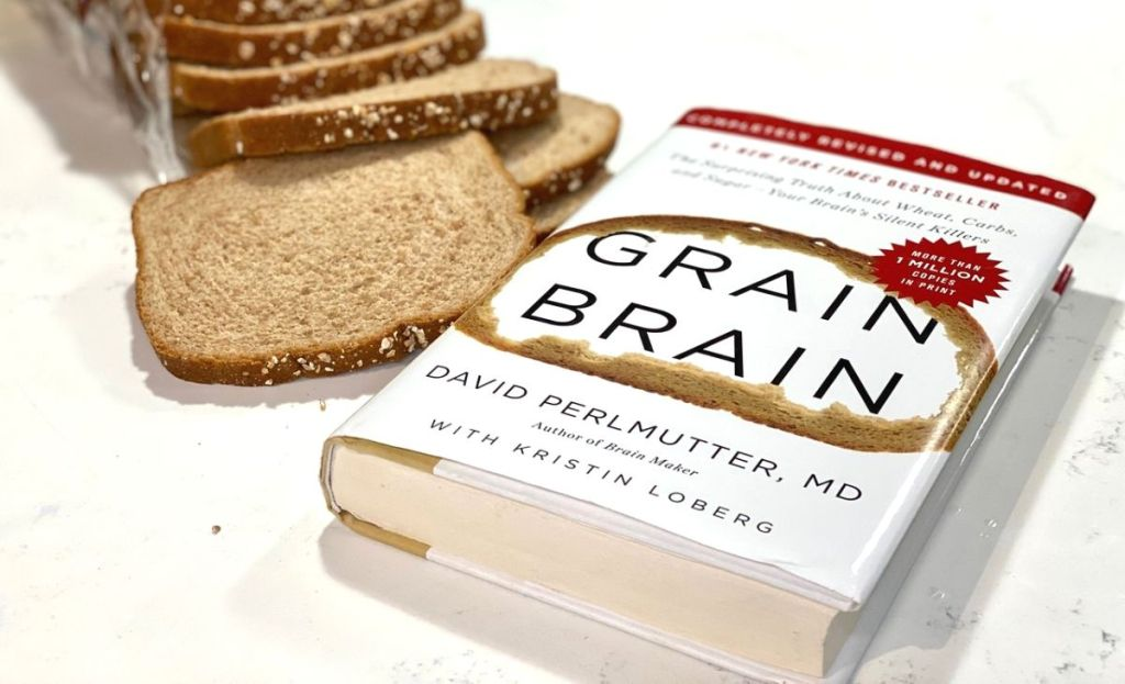 A Grain Brain hardcover book on the counter next to slices of bread