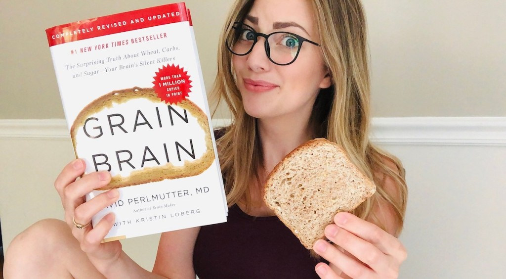 woman skeptical holding a grain brain book with piece of bread