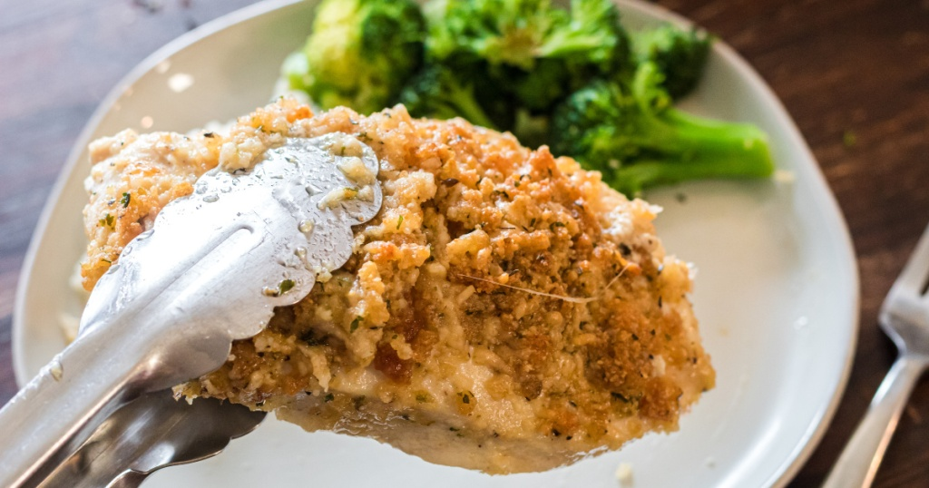Adding a Parmesan crusted chicken breast to a dinner plate