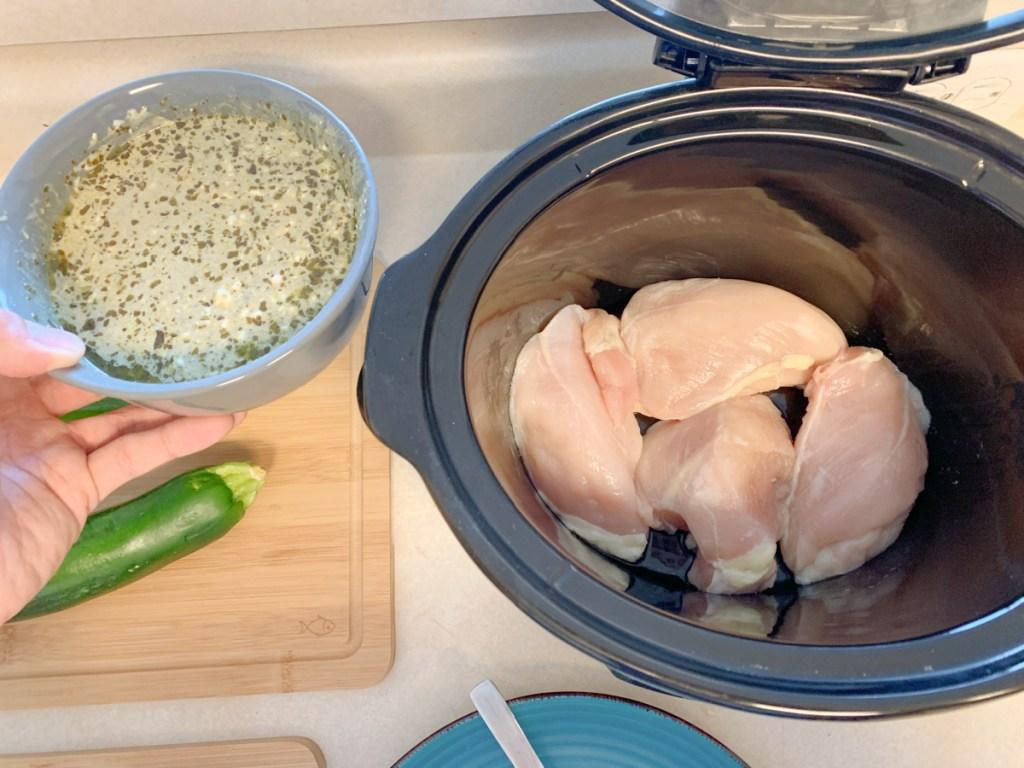 lemon pesto chicken adding sauce to slow cooker