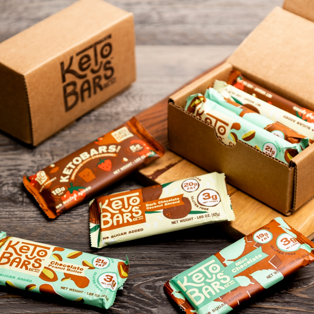 A sample box of keto bars next to some bars on a table