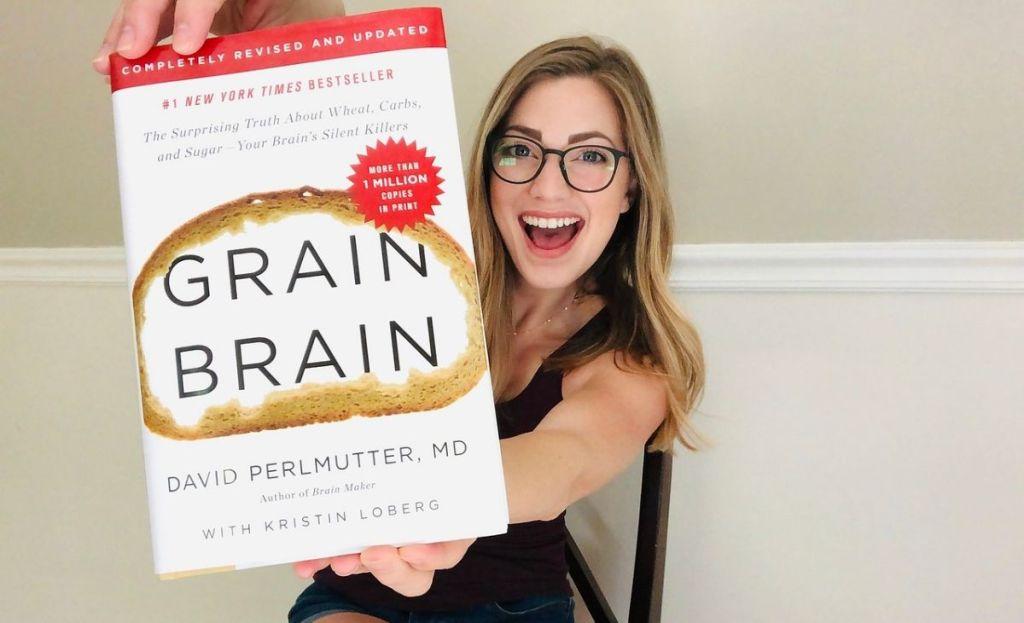 A woman holding a hard copy of Grain Brain