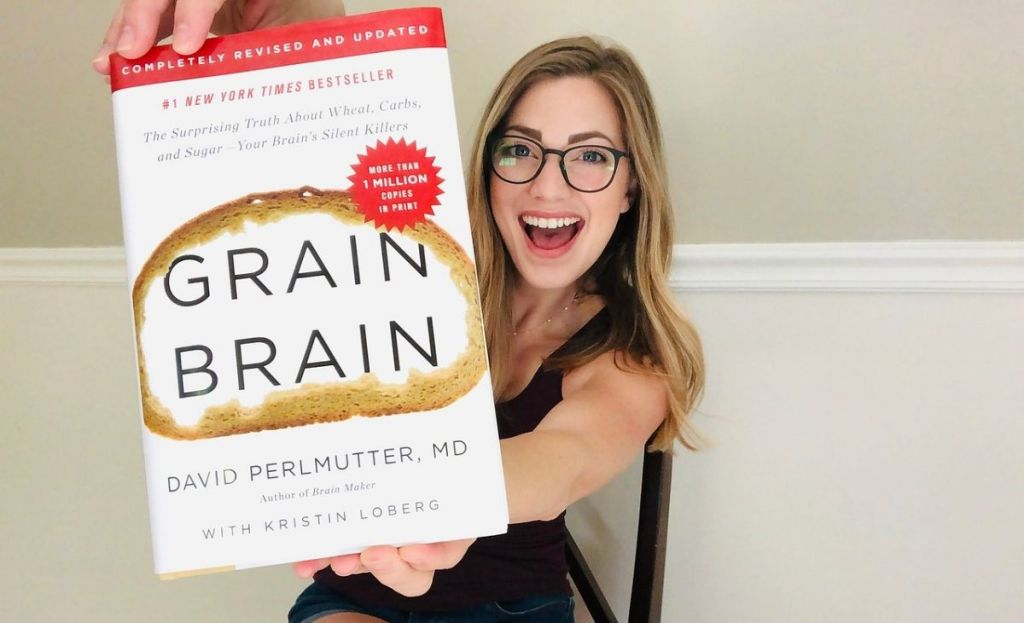 A woman holding a hard copy of Grain Brain
