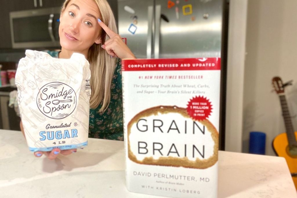 A woman holding a bag of sugar next to a hardcover of Grain Brain