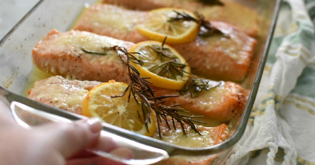 pulling out baked salmon with lemons