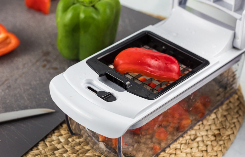 using a vegetable chopper to dice a red bell pepper