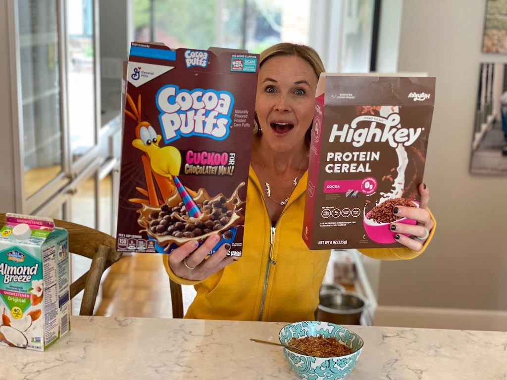 woman holding up Cocoa Puffs and HighKey protein cereal boxes