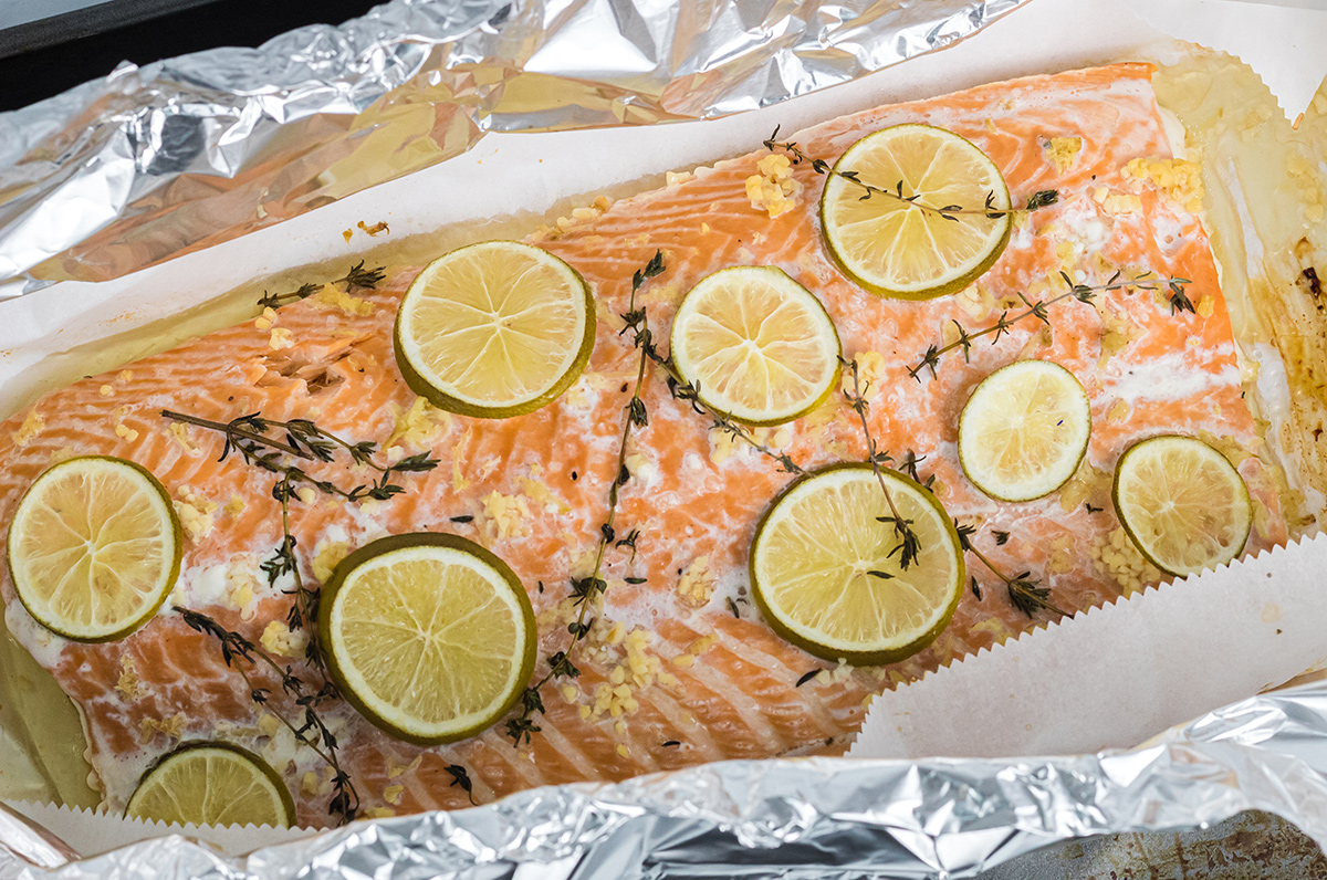 large piece of salmon with citrus and fresh herbs