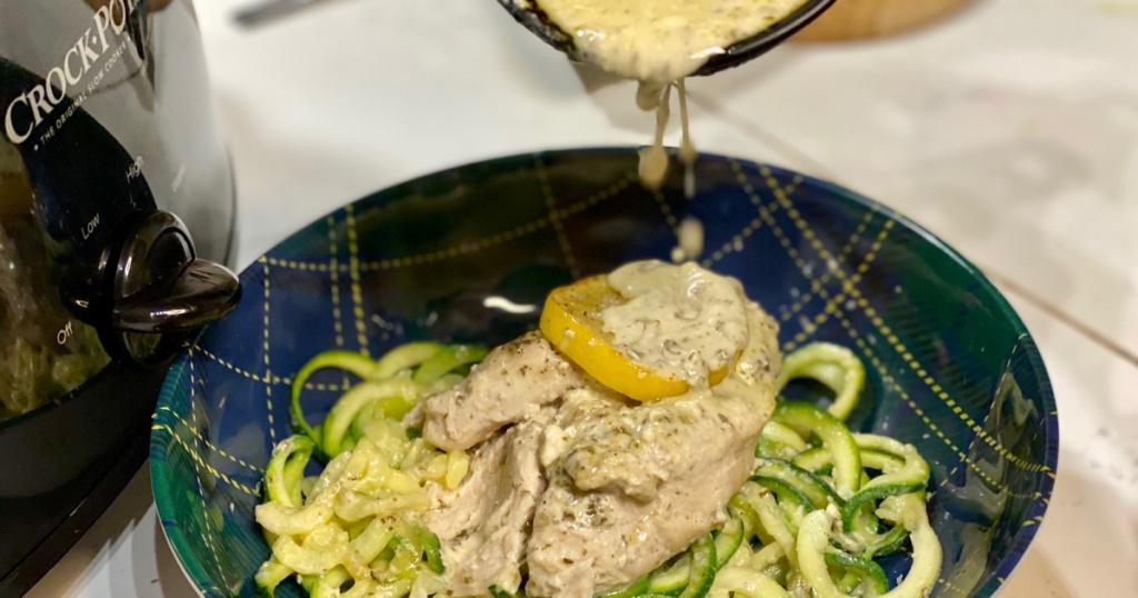 putting lemon pesto sauce on chicken
