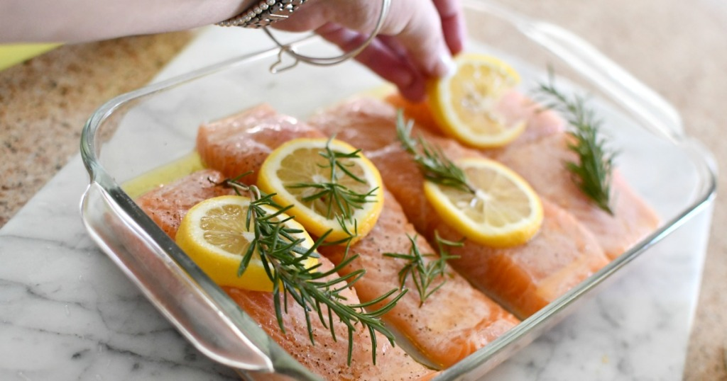 placing lemon slices and sprigs of rosemary on top of the salmon
