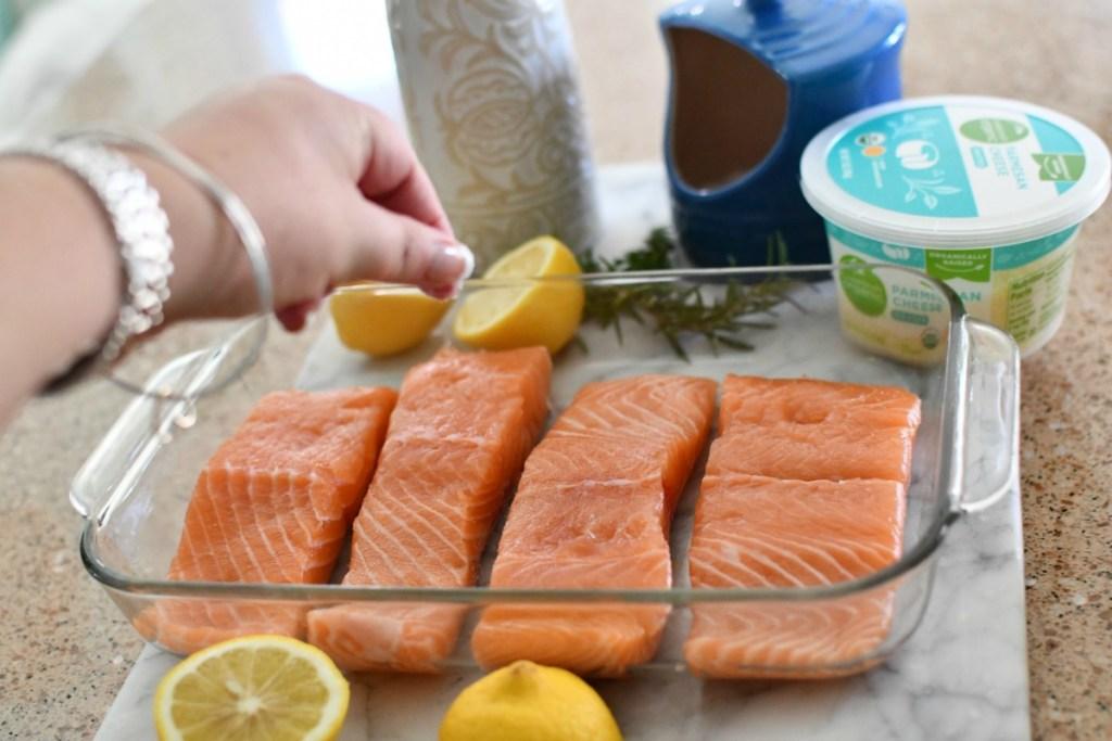 sprinkling salt over salmon filets