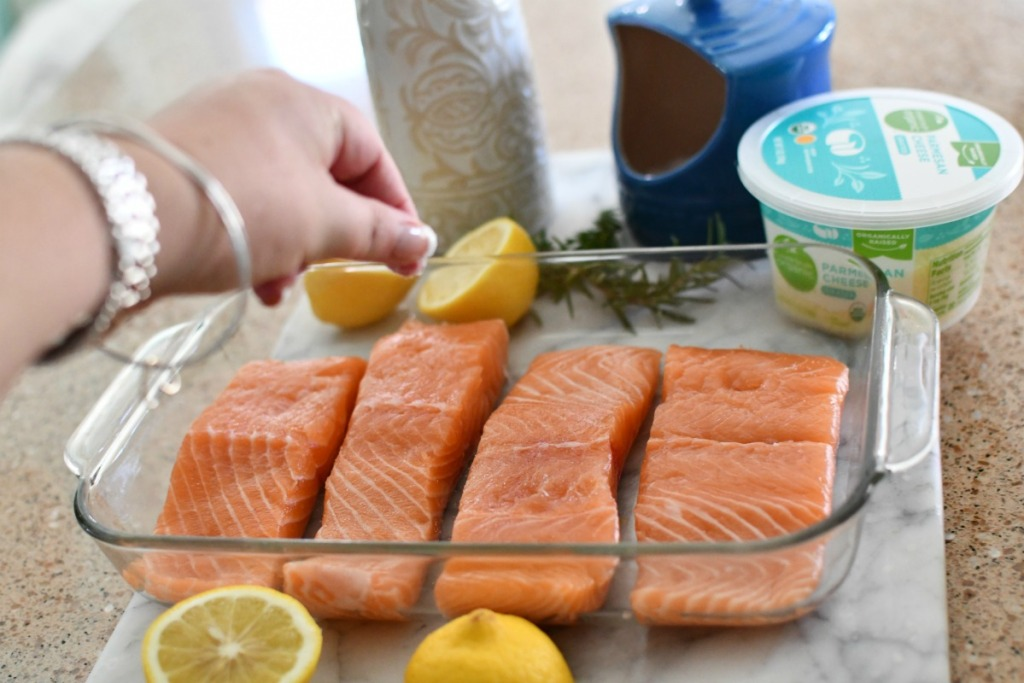 sprinkling salt over salmon filets
