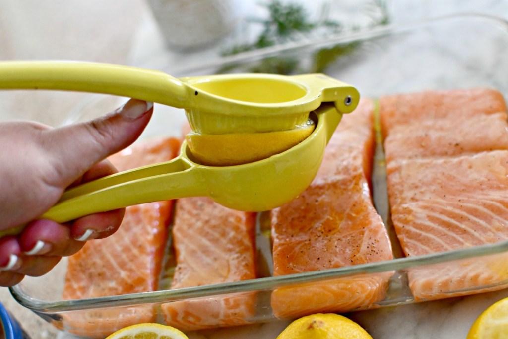 using a citrus juice to squeeze lemon juice on salmon