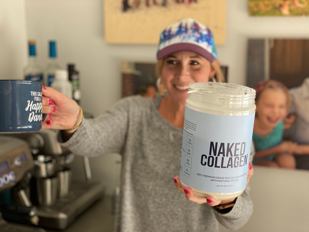 woman holding Naked Collagen tub and coffee cup