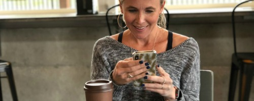 woman texting with coffee