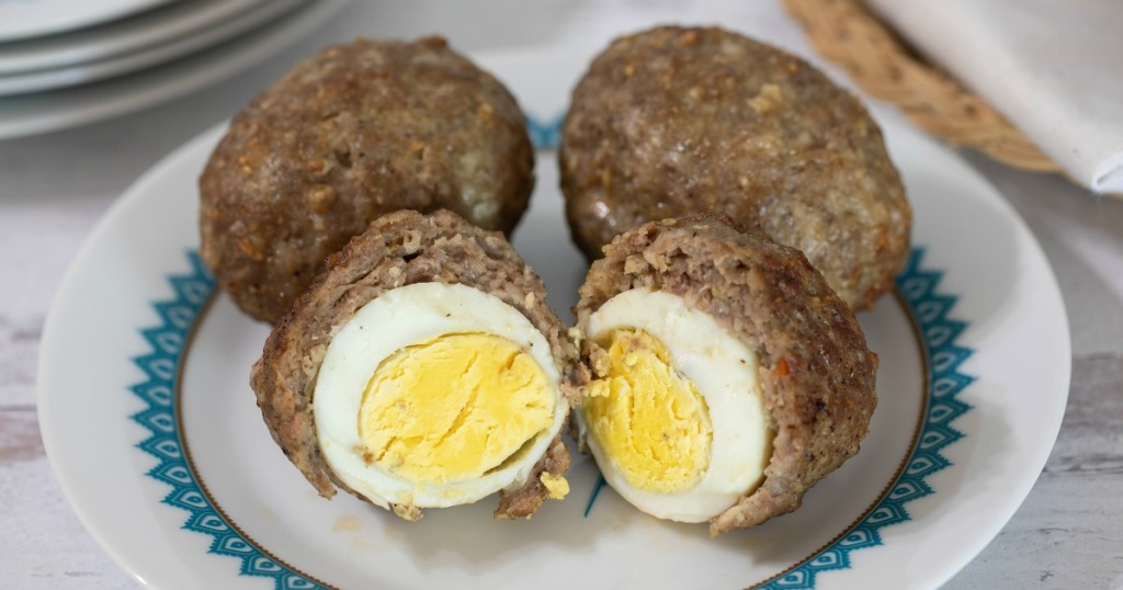 2 scotch eggs on a plate cut open