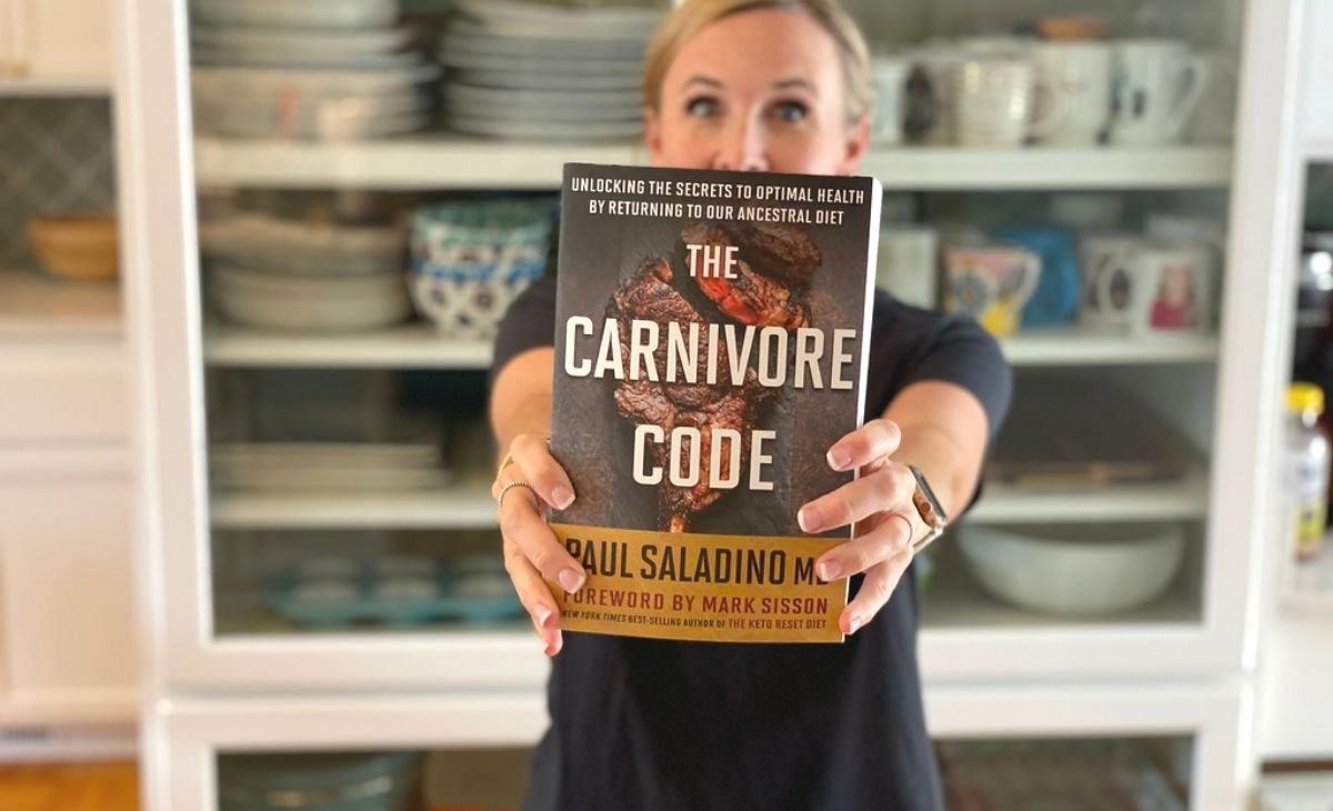 A woman holding up a book in front of her face
