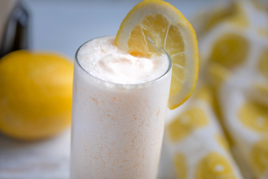 frosted lemonade with lemon wedge on glass
