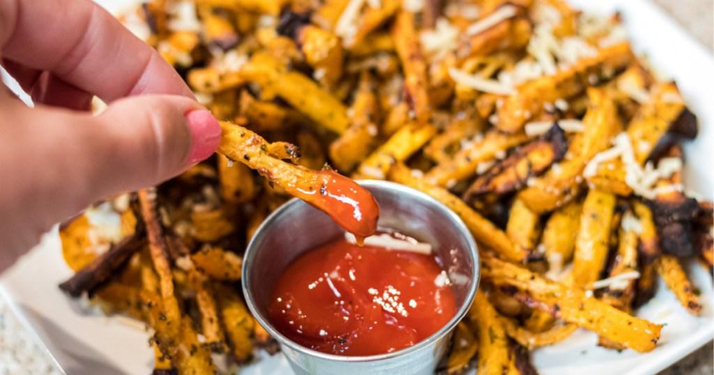 dipping rutabaga fries into keto ketchup