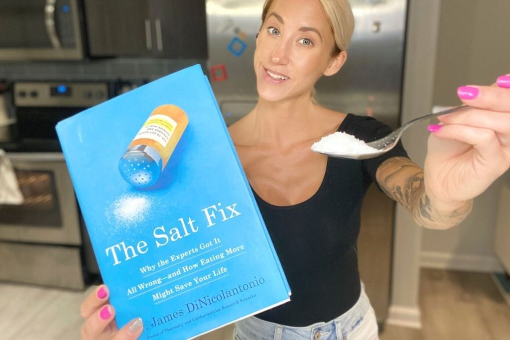 A woman holding a book and a spoonful of salt