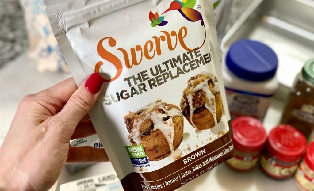 A hand holding a bag of keto sugar free Swerve Brown sweetener