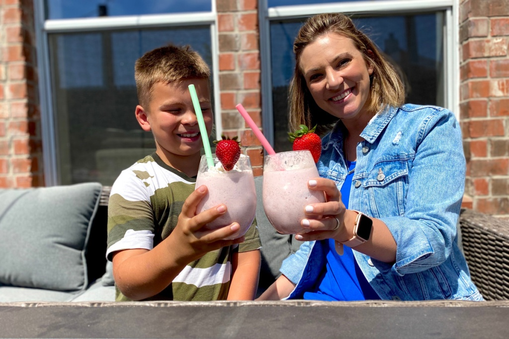 woman and boy holding up keto strawberry banana smoothies