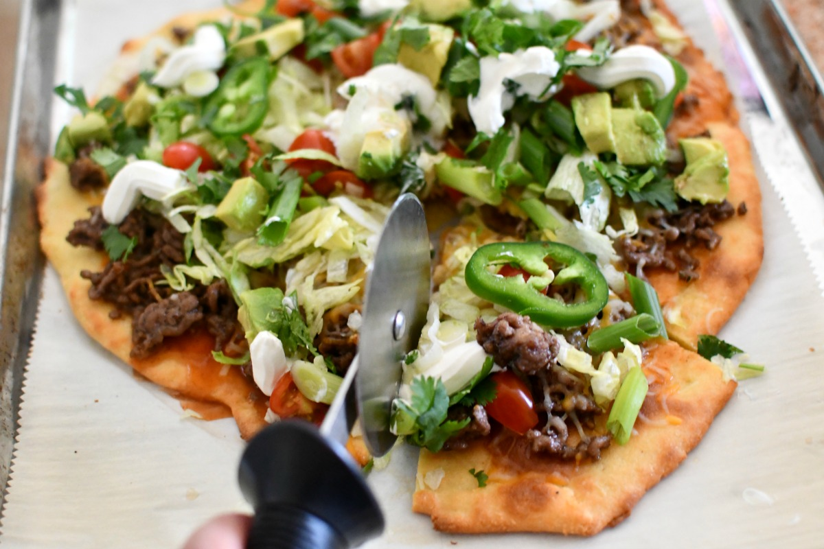 cutting a keto mexican taco pizza