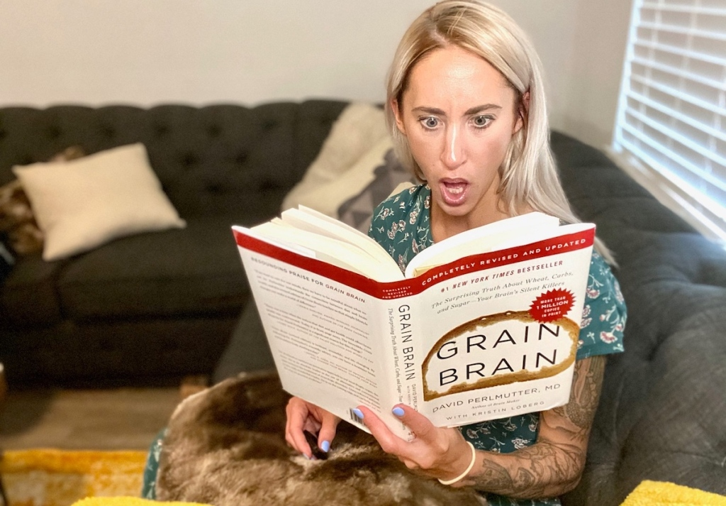 woman holding grain brain book looking shocked sitting on couch