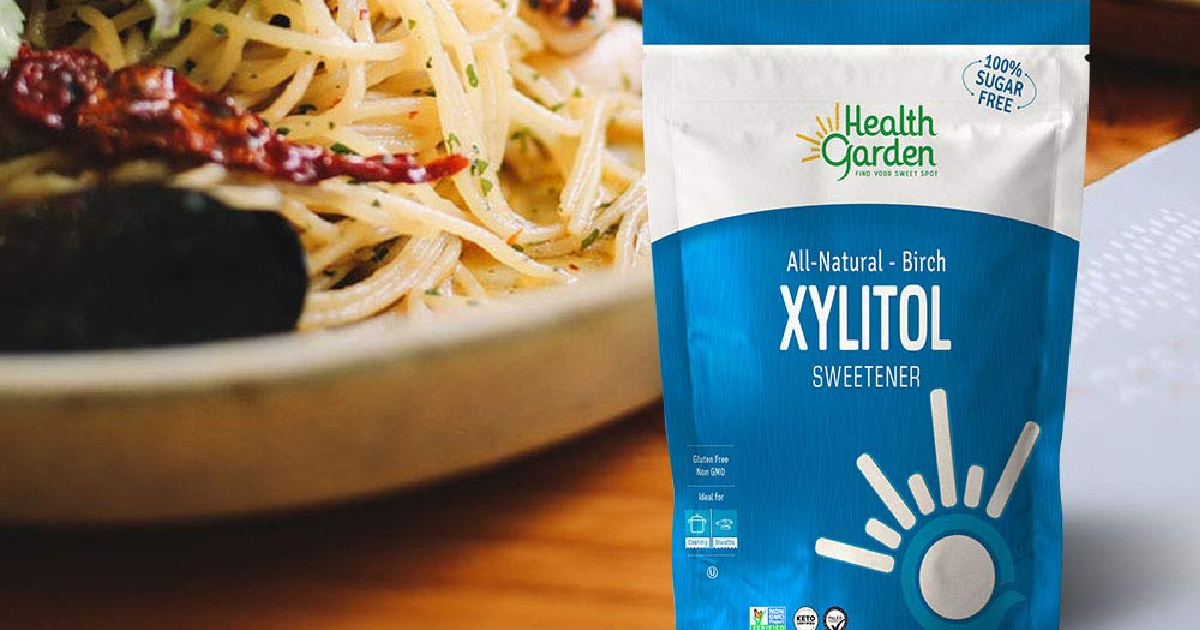 Health Garden Xylitol Sweetener Bag on wood counter with bowl of pasta in background