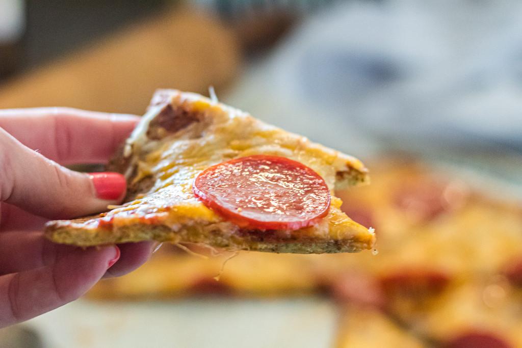 holding slice of pork rind pepperoni pizza
