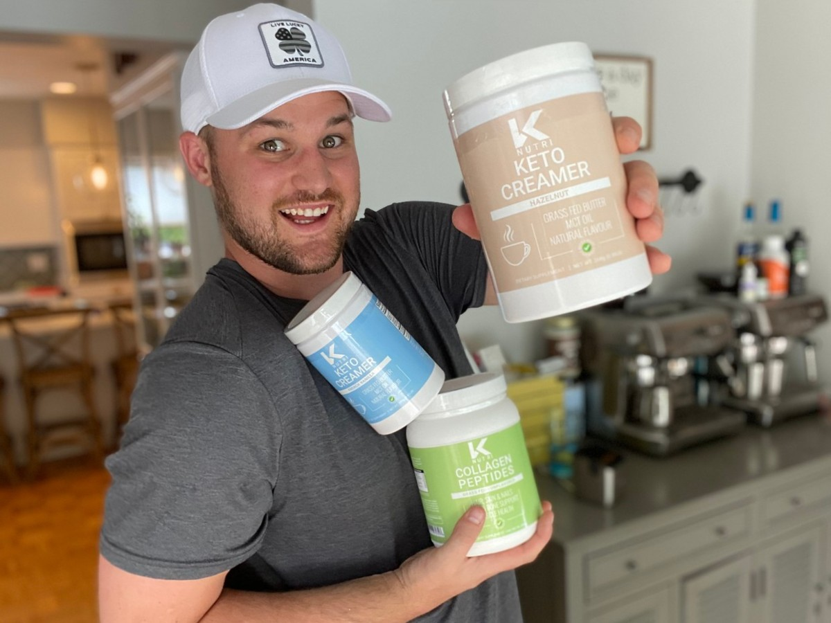 man holding 3 canisters of powdered keto products
