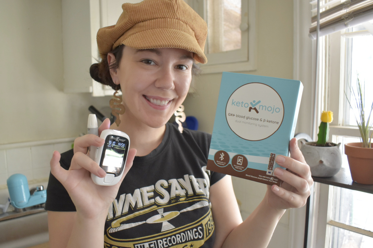 woman holding keto mojo case and monitor