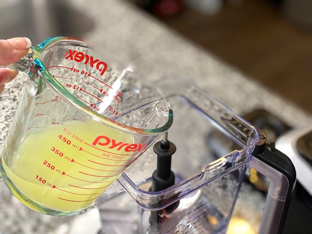 pouring lemon juice into a blender