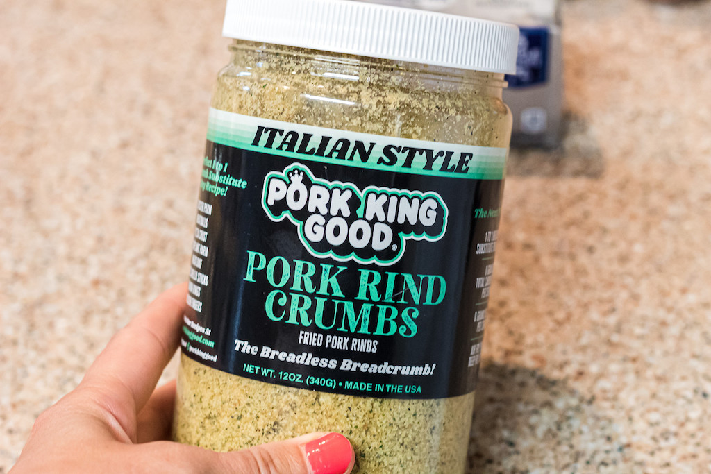 holding pork king good pork rind crumbs container