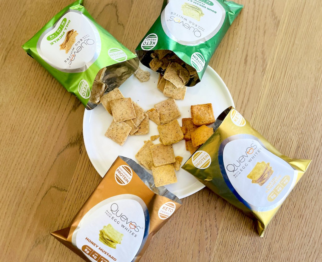 four quevos chip bags laying on table with chips spilling on white plate