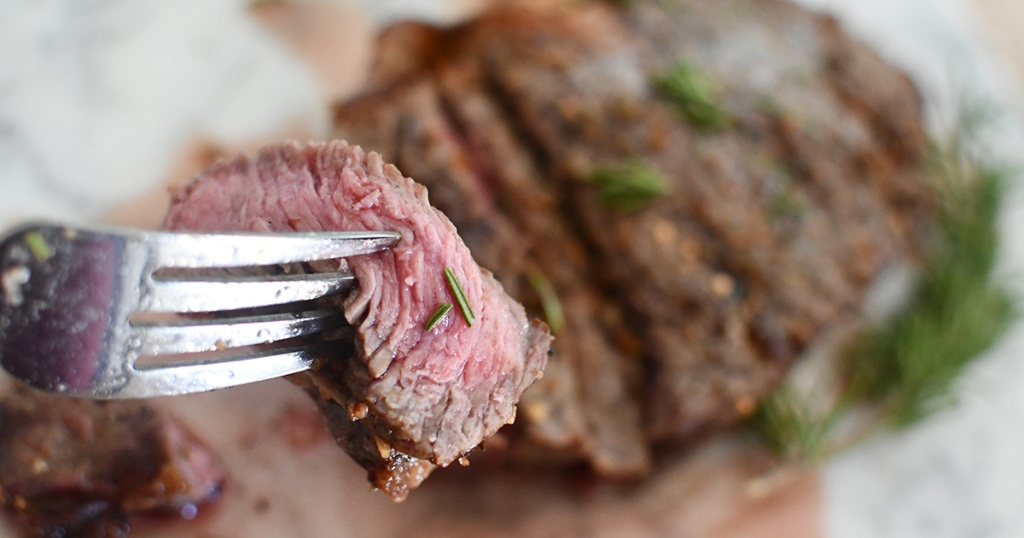 fork holding up piece of steak from the air fryer