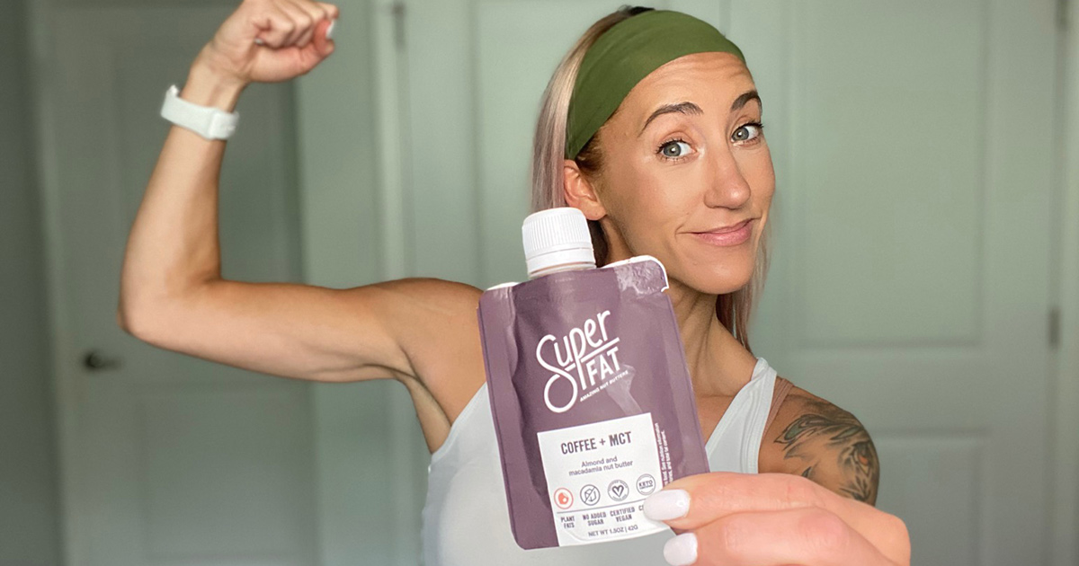 woman flexing bicep holding up superfat coffee peanut butter pouch
