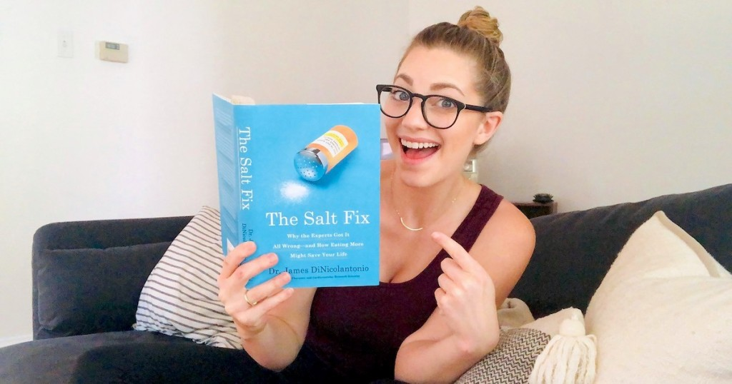woman holding the salt fix book pointing to front cover smiling
