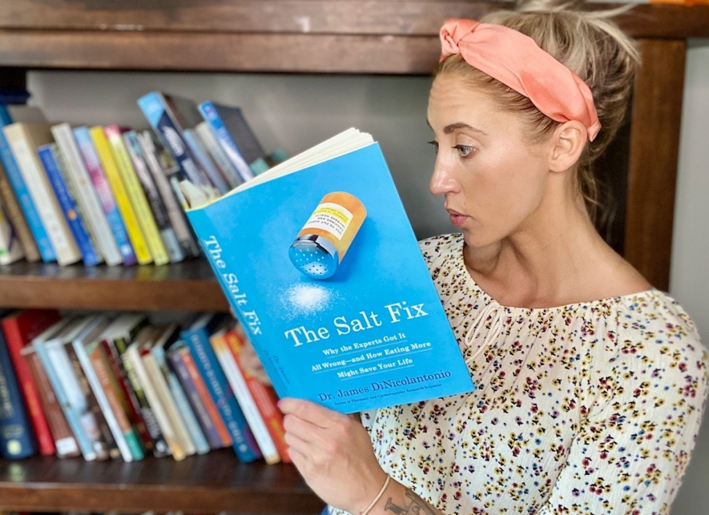 woman reading the salt fix book in front of book shelves