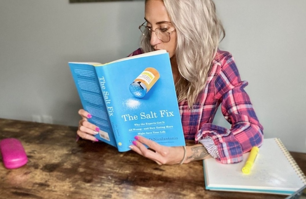 woman holding blue the salt fix book wearing glasses and plaid shirt