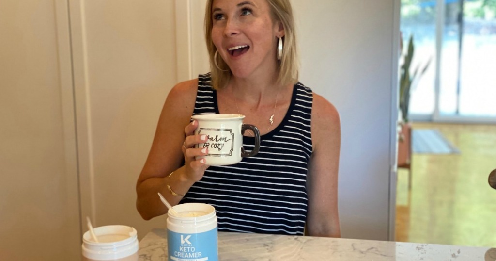 woman holding coffee cup with keto coffee creamer on counter