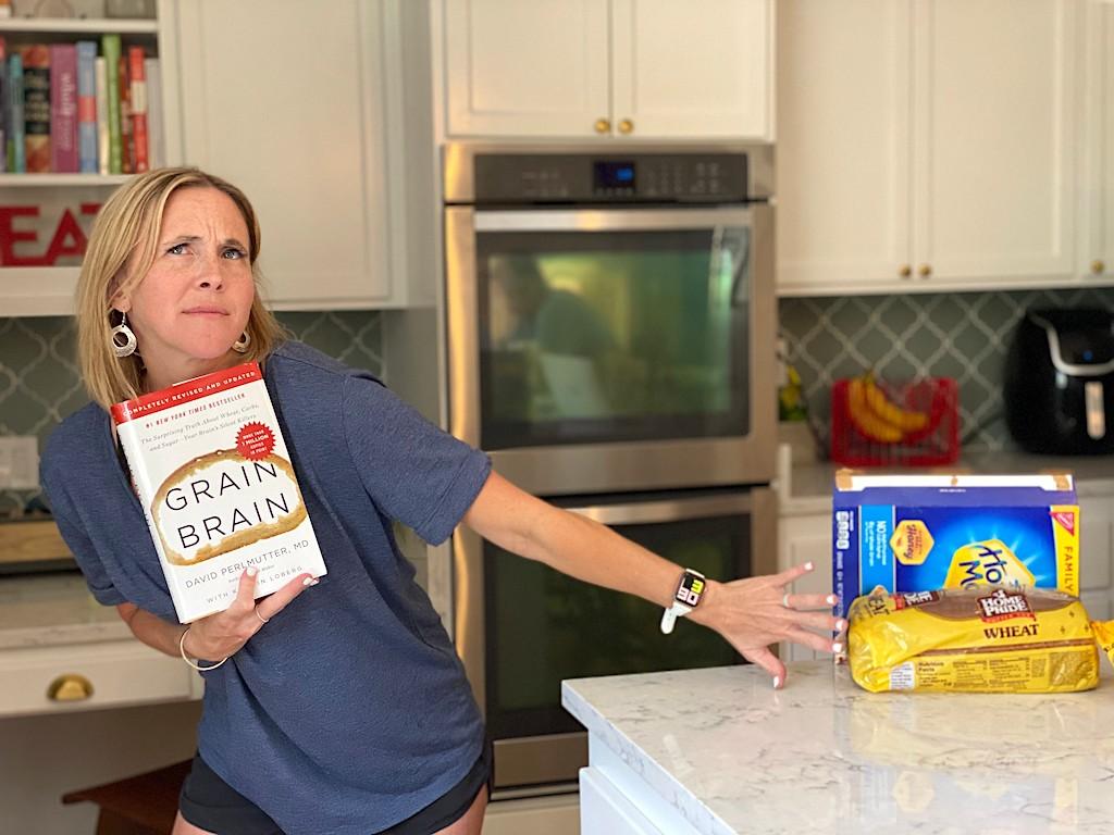 woman holding Brain Grain book while pushing away carbs