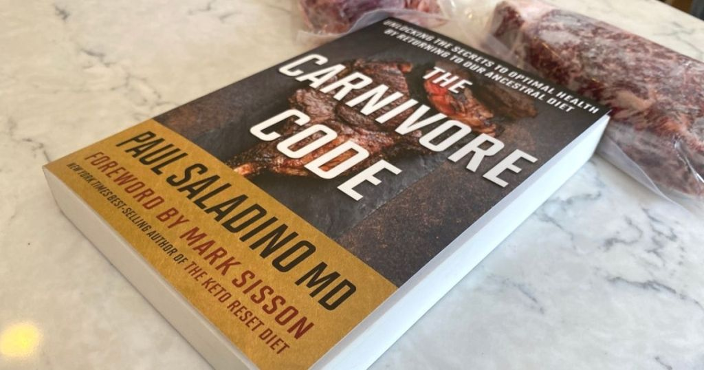 A book on a counter next to some steaks