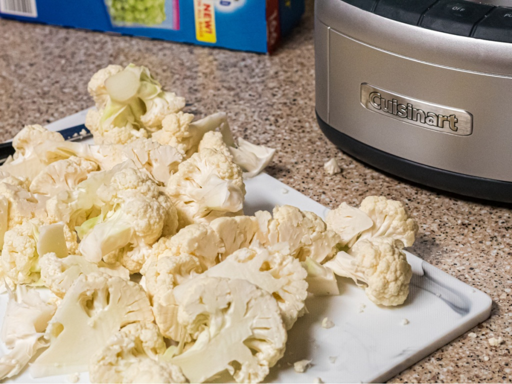 cauliflower cut up on cutting board