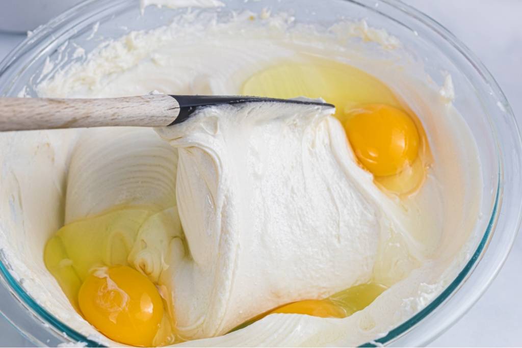 folding cream cheese and eggs in a bowl