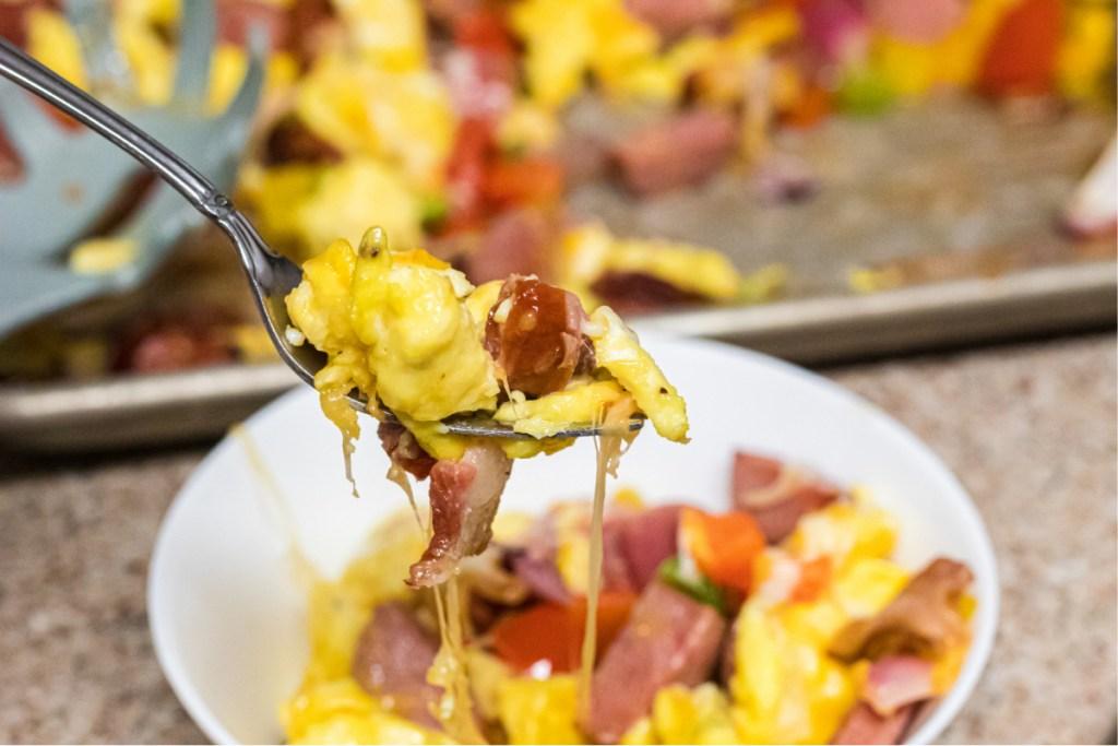 taking bite of keto scrambled eggs and sausage